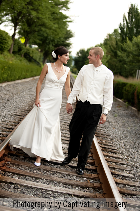 bride and groom photographed on train tracks