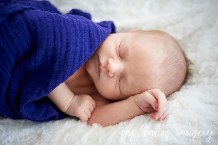 sleepy baby in gauze swaddle
