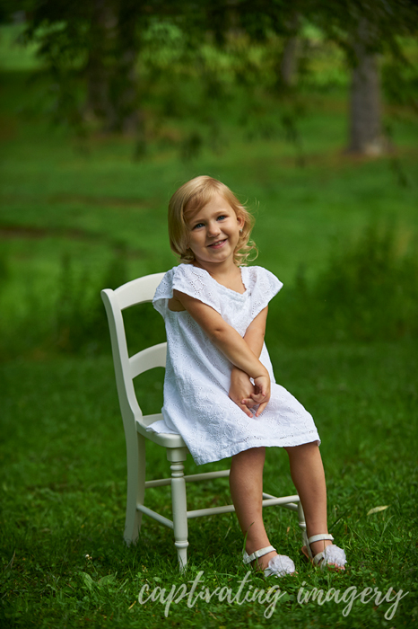 little girl sitting pretty on a chair