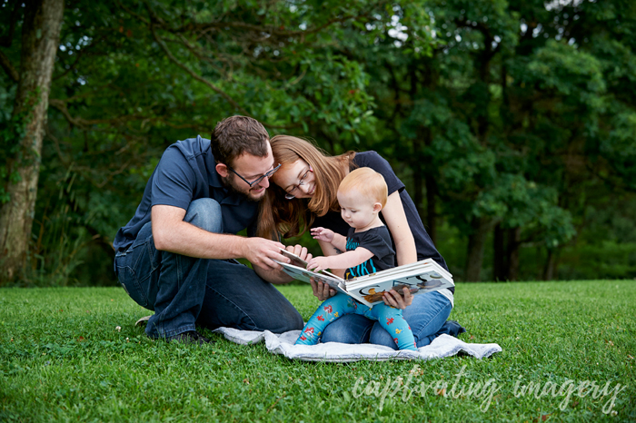 mom and dad reading to their daughter