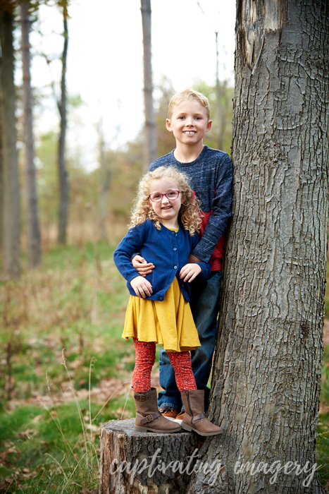 brother and sister on a tree stump